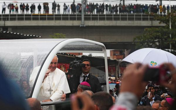 Francis waves to the crowd while riding in the Popemobile as he tours the Varghina favela in Rio de Janeiro.