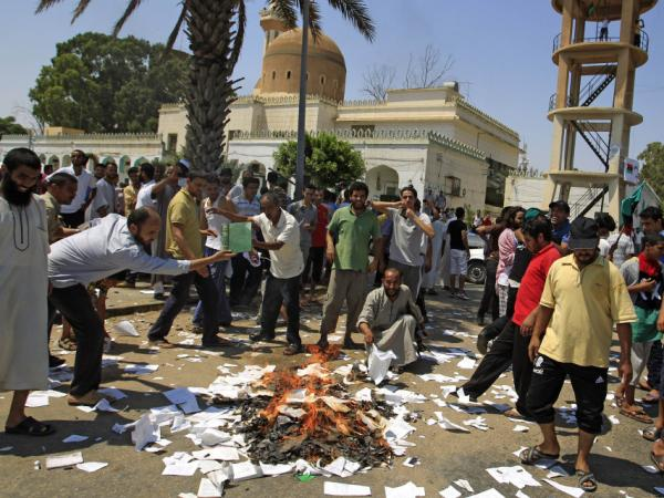 Rebel supporters burn books on the philosophy of Gadhafi in Tripoli on Saturday.  Libyan rebel leaders say they're negotiating with regime loyalists in holdout towns.