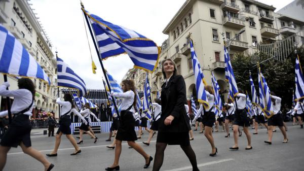 <p>A teacher walks by during a parade in the northern Greek city of Thessaloniki on Thursday. Parades were held across Greece on Thursday to mark the 61st anniversary of the country's resistance to Axis forces, which dragged Greece into World War II. Some bystanders also seized the opportunity to shout anti-austerity slogans.</p>