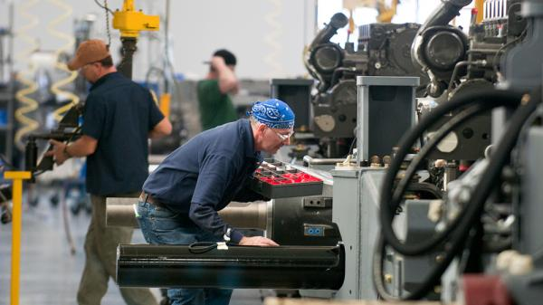 AGCO employees work on the assembly line in the company's newly expanded Jackson, Minn., manufacturing plant. The expansion brought the facility's staff from 850 to 1,050 workers and allows the plant to make tractors that were previously made in France.