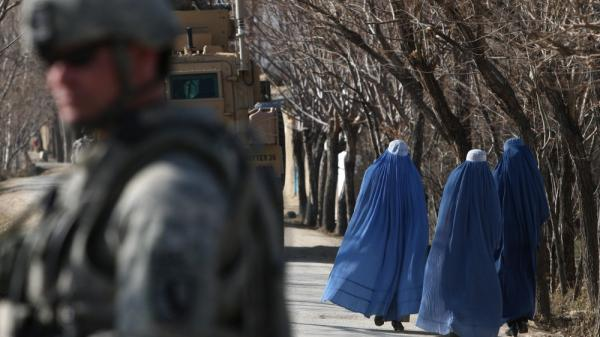Afghan women pass U.S. soldiers near Bagram Air Base outside Kabul in 2010. While conditions for Afghan women have improved over the past decade, but they still face many restrictions, as well as abuses like honor killings.