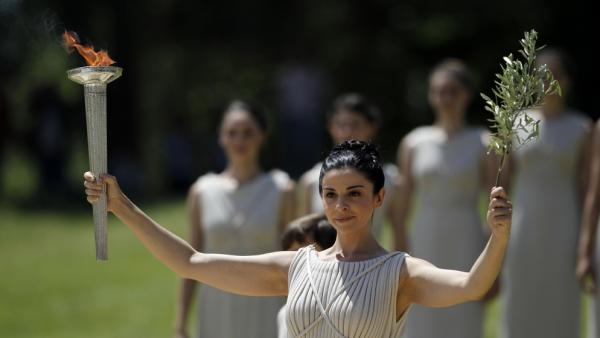 A priestess holds an olive branch and the lit Olympic torch.