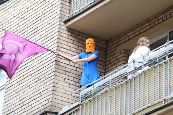 A supporter of feminist punk band Pussy Riot wearing the group's trademark colored balaclava waves a flag on a balcony in Moscow on Friday.