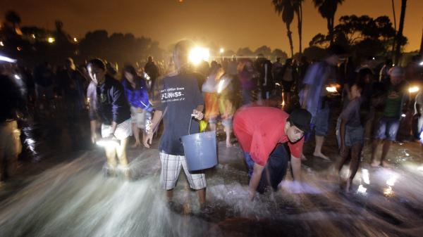 People stand on the beach to catch grunion during the annual grunion run at Cabrillo Beach in San Pedro, Calif., in 2009.