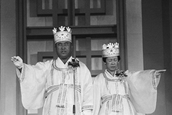 Moon and his wife participate in the traditional invocation of a blessing at a mass wedding in Seoul's Chamsil gymnasium, where 6,000 couples from about 80 countries were married in 1982.