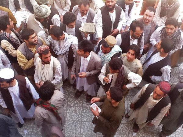 Money-changers in the Afghan city of Herat carry large stacks of Iranian currency.