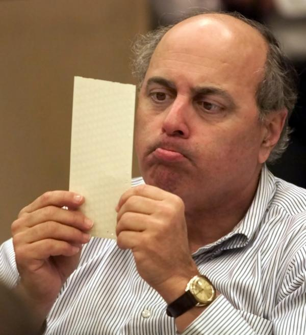 Broward County canvassing board member Judge Robert Rosenberg examines a disputed ballot Nov. 24, 2000, in Fort Lauderdale, Fla.