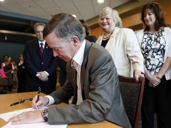 Colorado Gov. John Hickenlooper signs a bill in June 2011 to pave the way for a health insurance exchange in the state.