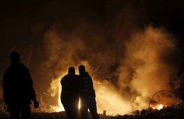 Palestinians try to extinguish fire following an Israeli air strike on Wednesday in Gaza City.