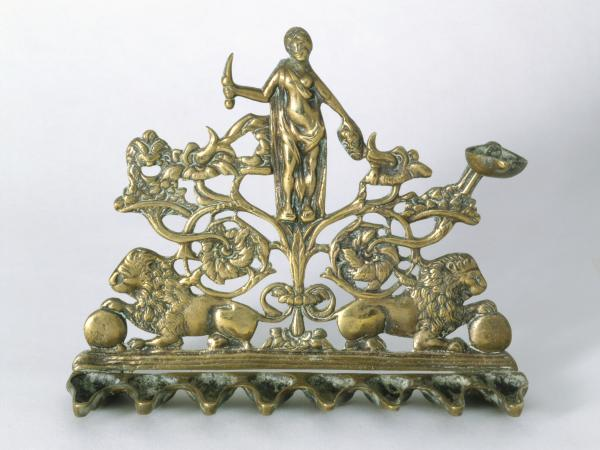 This Hanukkah lamp, made in Italy in the 19th century, depicts Judith holding a sword in one hand and the severed head of Holofernes in the other.
