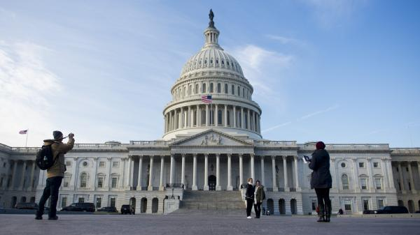 Tourists take photographs in front of the U.S. Capitol on Jan. 2, the day after Congress passed a bill to avoid the fiscal cliff.