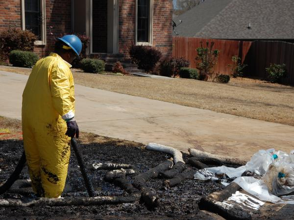 A worker cleans up oil in Mayflower, Ark., on Monday, days after a pipeline ruptured and spewed oil over lawns and roadways.