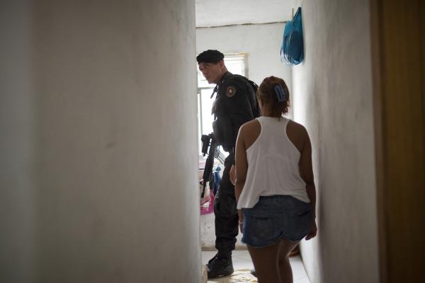 A police officer inspects a resident's home for weapons and drugs in the Parque Alegria <em>favela</em> in Rio in March.
