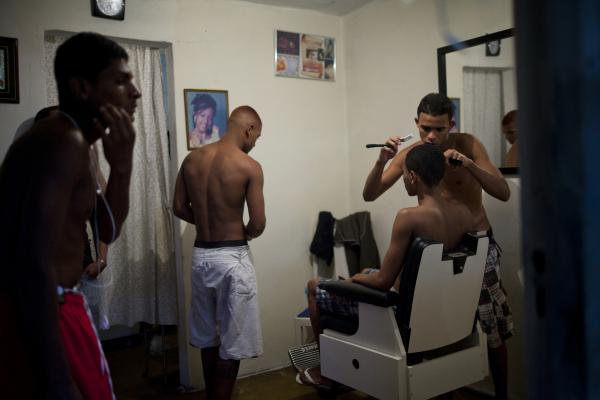 Mateus, 22, who opened a barbershop in his Rio home, shaves his friend's head. Since the pacification program began, more residents say they are moving around more freely in neighboring communities.