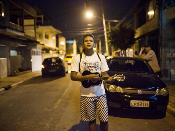 As the streets clear during the evening hours, a young man plays a ukelele-like instrument called a <em>cavaquinho</em> in a residential neighborhood of Mage, where residents can hear evidence of increasing gun power.