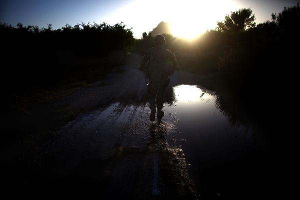 A U.S. soldier walks down a dirt road during the final U.S. patrol near the village of Arghandab, near Kandahar in southern Afghanistan. The area has long been a Taliban stronghold, and the Americans were turning the area over to the Afghan army.