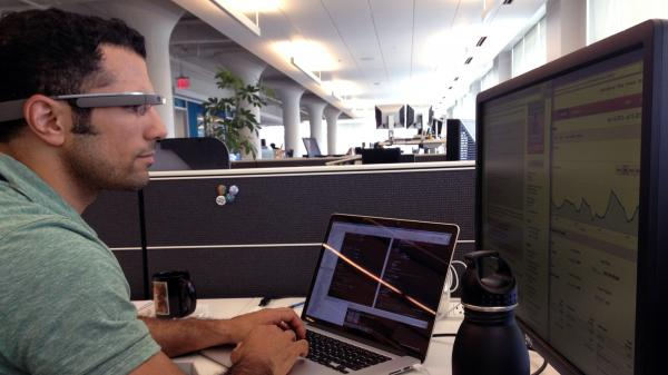 NPR developer Michael Seifollahi wears Google Glass while working at his desk.