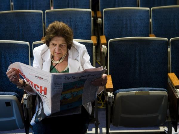 Helen Thomas reads the newspaper while sitting in her chair in the White House press room in 2006. She died on Saturday at age 92.
