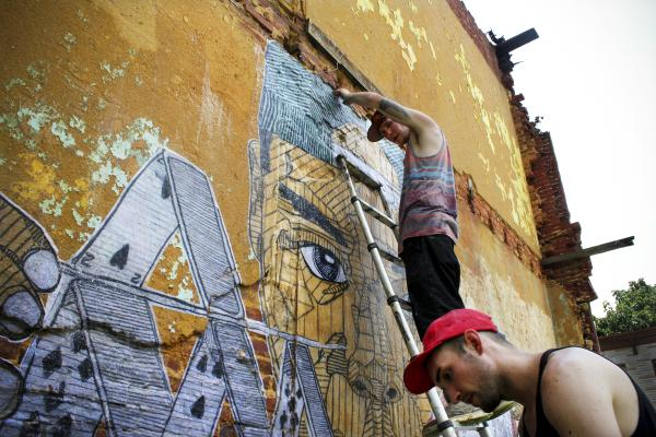 Street artists Nether (top) and Tefcon install a mural in the Johnston Square neighborhood of East Baltimore.