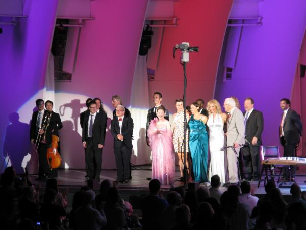 Pink Martini taking a bow at the end of the show. Bandleader Thomas Lauderdale in the red bowtie, Saori Yuki in pink, China Forbes in green, Storm Large in white, clarinetist Norman Leyden next to Storm. And back row center, our own Ari Shapiro.