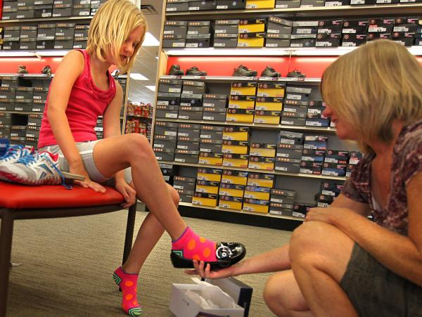 Chris Viehland helps her daughter Jenna try on shoes for the new school year at a Famous Footwear store in Fenton, Mo., Aug. 9, 2012.