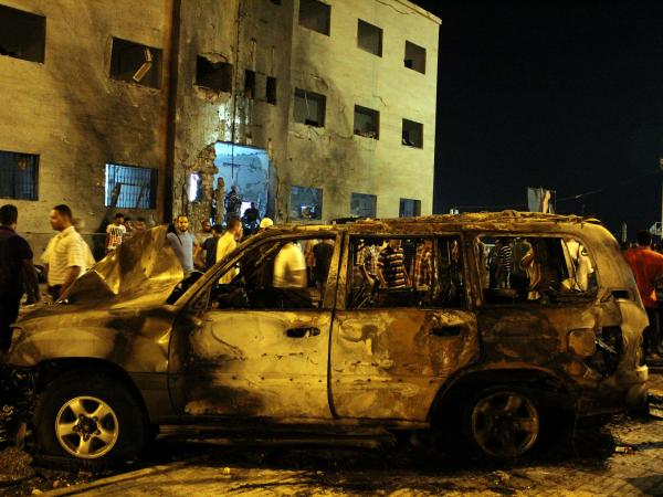 Libyans gather near a burned-out vehicle after an attack outside the courthouse in Benghazi on July 28, the day after more than 1,000 inmates escaped during a prison riot.