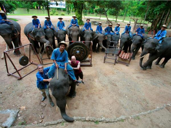 Thai Elephant Orchestra co-founder David Sulzer (bottom center, in red) poses with the animals and their mahouts, or keepers.