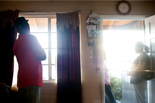 Francisco Duran scans the street from his window before stepping out to drive his mother to English class. He had just warned his friends on Facebook that a sherriff's deputy was a few blocks from his home on Phoenix's west side.