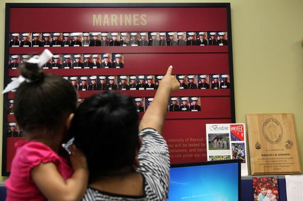 Victor's sister shows her daughter what he will wear when he is a Marine.