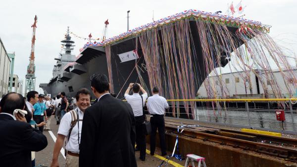 Japan's new warship, the <em>Izumo</em>, draws a crowd for its launch ceremony at the port in Yokohama Tuesday. At 248 meters (814 feet) in length, the flat-topped ship has been called a destroyer, or a helicopter carrier.