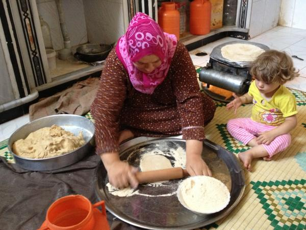 Um Ahmad, a woman in Taldo, bakes flatbread on an oil-operated portable stovetop.
