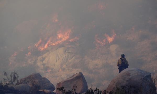 A firefighter watches a backfire burn while battling a wildfire, Thursday, Aug. 8, 2013, in Banning, Calif. (Jae C. Hong/AP)