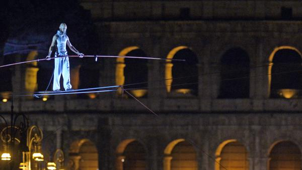 Tightrope walker Andrea Loreni performs in front of the Coliseum in Rome on Saturday. Rome's new mayor is on a crusade to make the ancient monuments more pedestrian friendly, and the city held an all-night street party as it permanently blocked off part of the main road running past the Coliseum.
