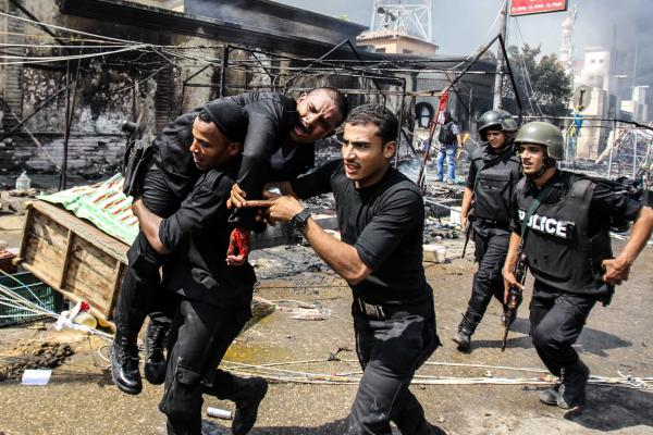 Policemen carry a wounded soldier near the Rabaa al-Adawiya mosque in Cairo. Police have taken full control of the two major squares Morsi supporters had occupied for several weeks.