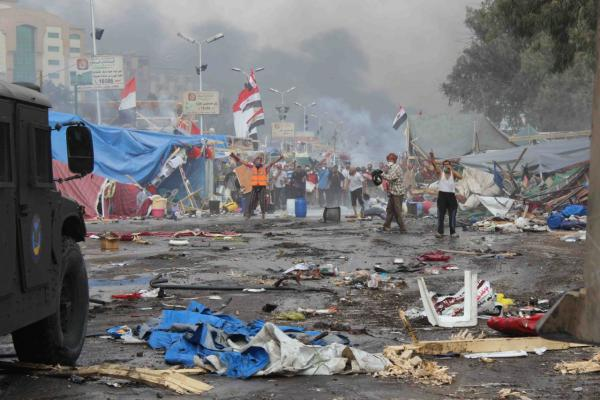 Supporters of ousted Islamist President Mohammed Morsi, stand among debris and smoke in background as they confront Egyptian security forces trying to clear the smaller of the two sit-ins, near the Cairo University campus in Giza, Cairo, Egypt, Wednesday, Aug. 14, 2013. (Imad Abdul Rahman/AP)