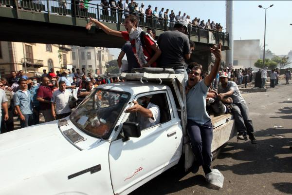 Demonstrators carry a wounded man after clashes with police near Ramses Square in Cairo.