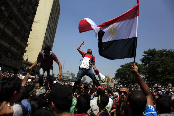 Supporters of Egypt's ousted President Mohamed Morsi chant slogans during a protest in Ramses Square in Cairo on Friday. Today's estimated death toll ranges from 60 according to the Associated Press and 95 according to Al Jazeera.