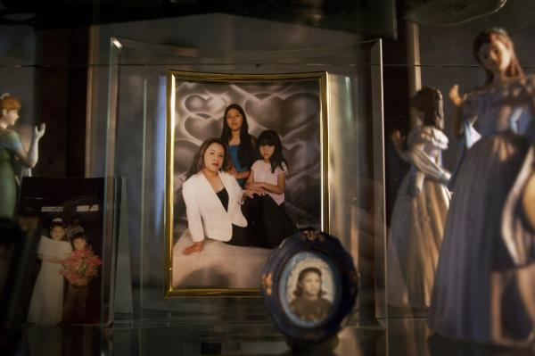 "A framed picture of Lily Ramos with her two girls at her home in Bend, Ore. She left the picture and her kids — Brian, Ashley and Karleen — with a relative when she was deported to Mexico. ""<em>No quiero que sufren</em>,"" she said. ""I don't want them to suffer."""