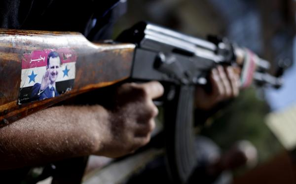"A Syrian military soldier holds his Ak-47 with a sticker of Syrian President Bashar Assad and Arabic that reads, ""Syria is fine,"" as he stands guard at a check point in Damascus, Syria, Wednesday, Aug. 21, 2013. (Hassan Ammar/AP)"