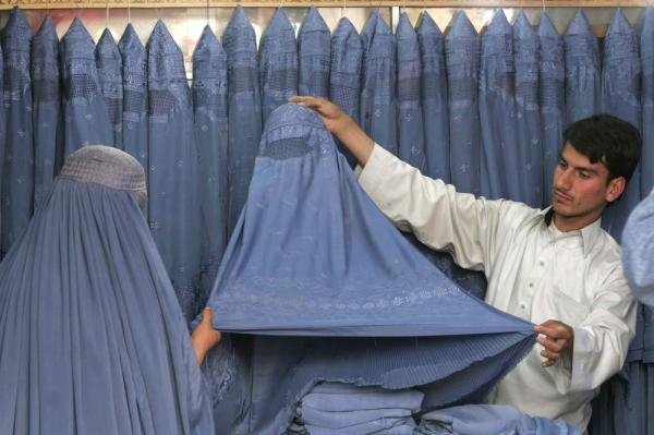An Afghan man displays a burqa to a woman at a burqa shop in the city of Herat province southwest of Kabul, Afghanistan April 2008. (Fraidoon Pooyaa/AP)