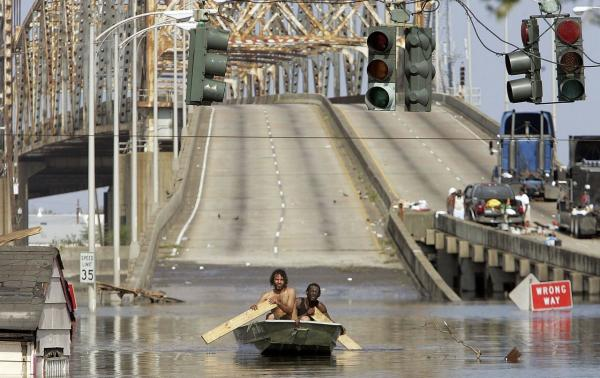 Two men paddle in high water after Hurricane Katrina devastated the area, August 31, 2005, in New Orleans, Louisiana. (PRNewsFoto/PBS)