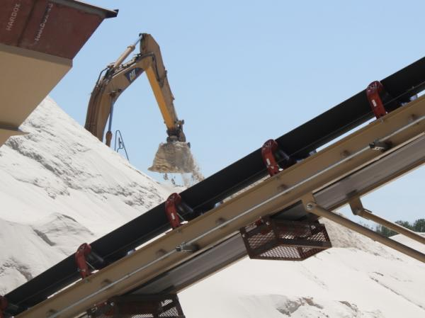 At the top of the bluffs, this backhoe shovels the sand that's been crushed and washed onto a conveyor belt that runs the sand through a drier before it's loaded into a rail car.