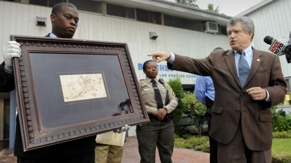 "Los Angeles Sheriff lead detective Clarence Williams, left,  and Los Angeles County sheriff's spokesman Steve Whitmore, right, display the recovered $250,000 quill pen Rembrandt drawing known as ""The Judgment."""