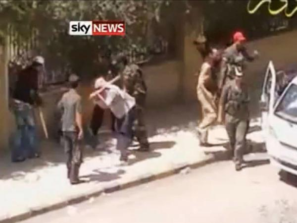 This screen grab, taken from an amateur YouTube video, shows a crowd beating a man in the eastern Syrian city of Deir al-Zour. This video cannot be independently verified.