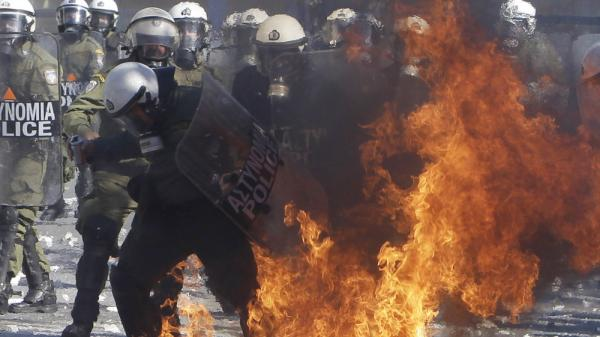 <p>A riot policeman's clothing catches fire after being hit by a gasoline bomb during clashes with protesters Wednesday outside the Greek Parliament in Athens.</p>