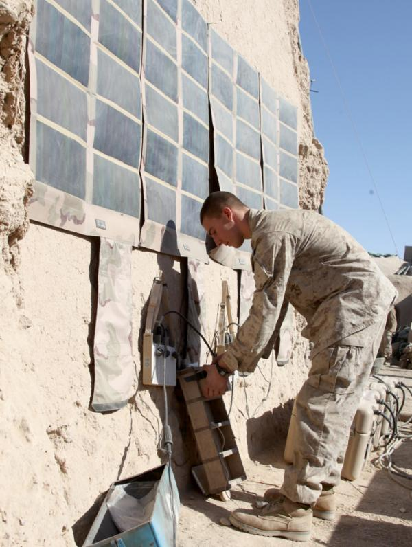 <p>Lance Cpl. Dakota Hicks, from Laharpe, Ill., connects a radio battery to a portable solar panel system in Sangin District, Afghanistan.</p>