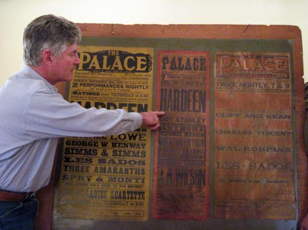 <p>George Hardeen poses with a poster from a 1906 performance by his grandfather, Theo Hardeen. It is the only memento he has of his grandfather. </p>