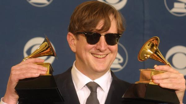 <p>T Bone Burnett holds two trophies, one for Producer of the Year, at the Grammy Awards in 2002.</p>