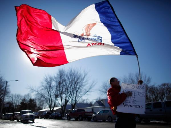 Edward Lewis of Council Bluffs waved an Iowa state flag outside the Family Table Restaurant in Atlantic on Sunday, before the arrival of former Massachusetts governor and Republican presidential candidate Mitt Romney.