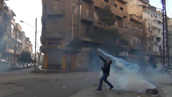 A protester in Homs throws a tear gas canister back at the security forces on Dec. 27, 2011.